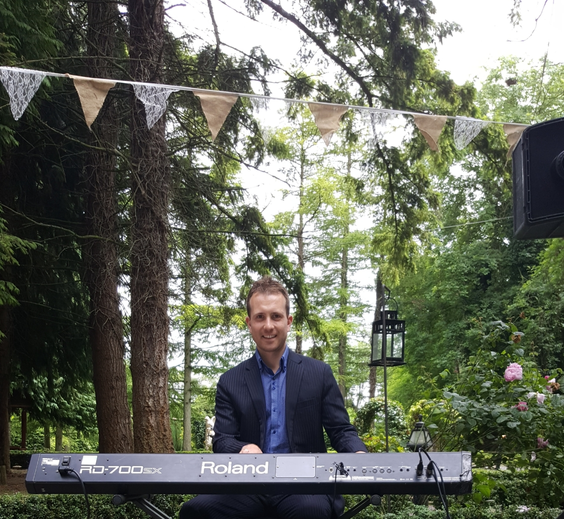 Joe Kenny playing piano in forest at outdoor civil ceremony